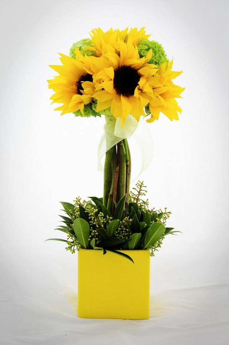Make a sunflower topiary with a small container (containing a block of Oasis), sunflowers, ribbon, and some greenery to cover the Oasis at the base.