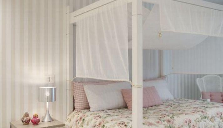 Cama estilo romântico, com roupa de cama floral, do projeto da arquiteta Izabela Lessa, para quarto de adolescente  Foto: Divulgação