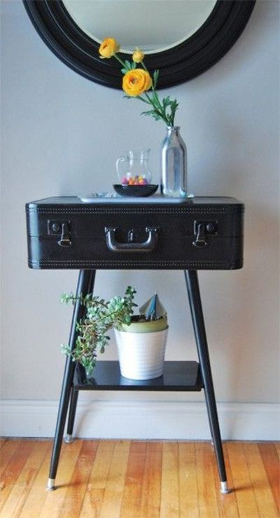 Fun night table or place to store your makeup: a suitcase spray-painted black with four table legs and bottom rack attached.