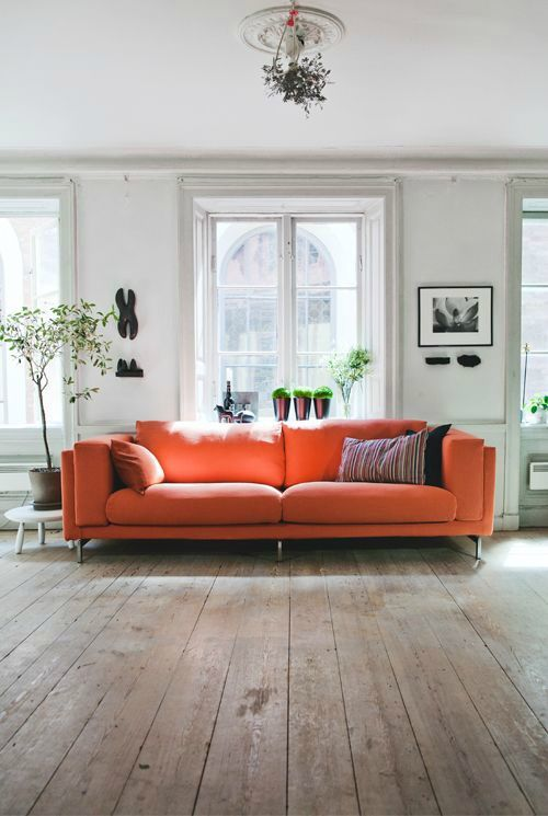 Bright couch, wide plank floors, plants, white walls. Peach Sofa + Entire Living  room ...