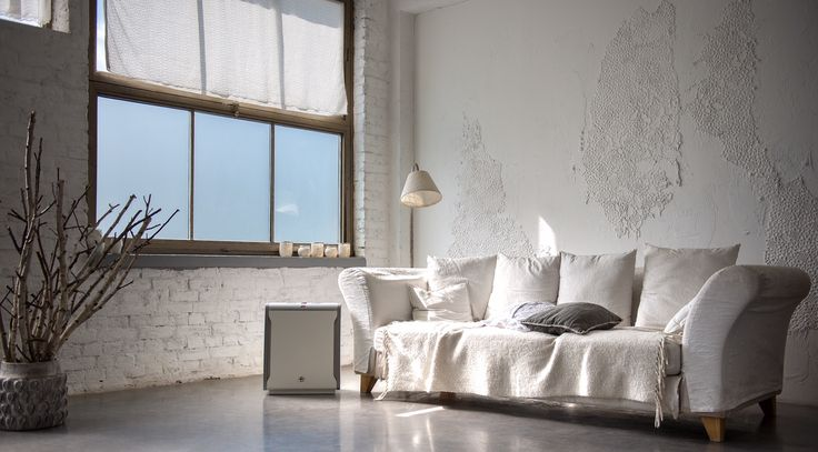 Minimalist-industrial loft with raw, white wall and Lux Aeroguard 4S air purifier.