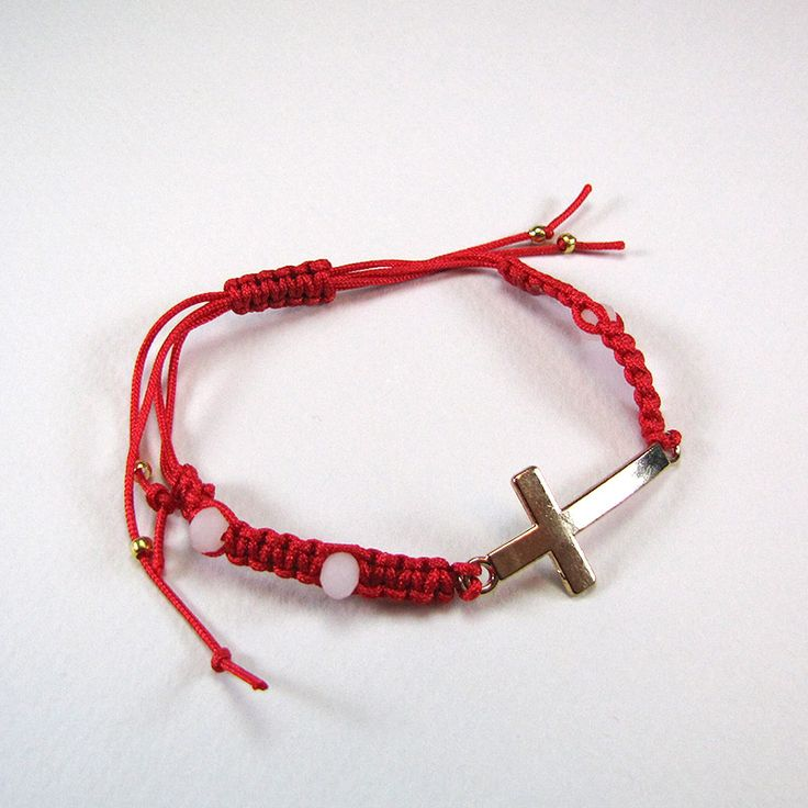 Adjustable macrame bracelet with red cord, white glass and golden beads and golden cross.