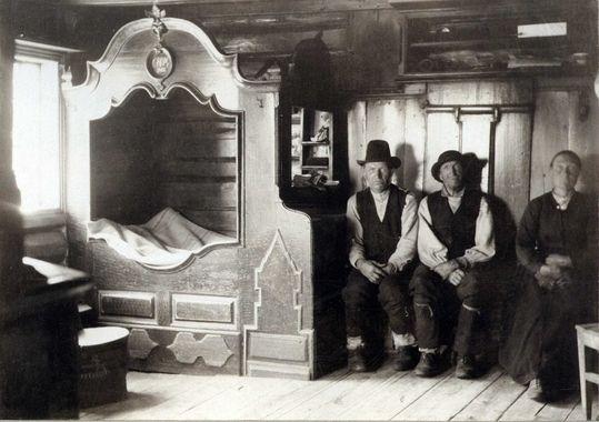 DigitaltMuseum - Interiør, stue, Søre Husevold, Husevolldalen. Tinn, Telemark. To menn og en kvinne sittende ved veggen. Seng. Fotografert 1907.