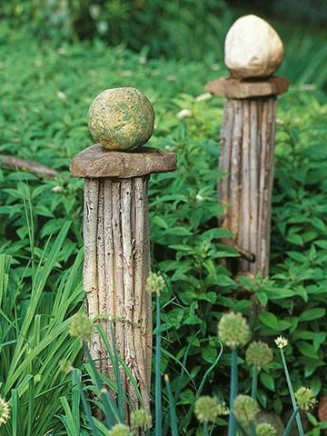 DIY garden art. Bundle sticks to create a decorative post, top it with a flat rock and place a round rock on top of that.