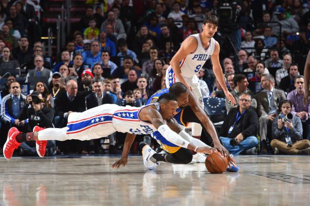 Robert Covington of the Philadelphia 76ers goes after a loose ball against Kevin Durant of Golden State Warriors at Wells Fargo Center on February 27...