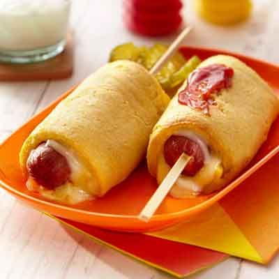 These hot dogs on-a-stick are surrounded by cheese and a cornmeal crust.