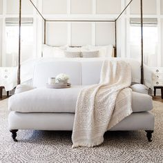 Bedroom decor ideas - soft, pale white colors, traditional style with metal canopy bed, sofa seating at end of bed.