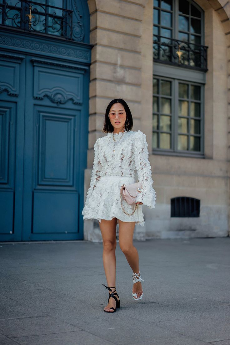 Aimee Song of the blog Song of Style shares an outfit post from Paris Fashion Week, wearing a Louis Vuitton white lace top and skirt to the Elie Saab show.