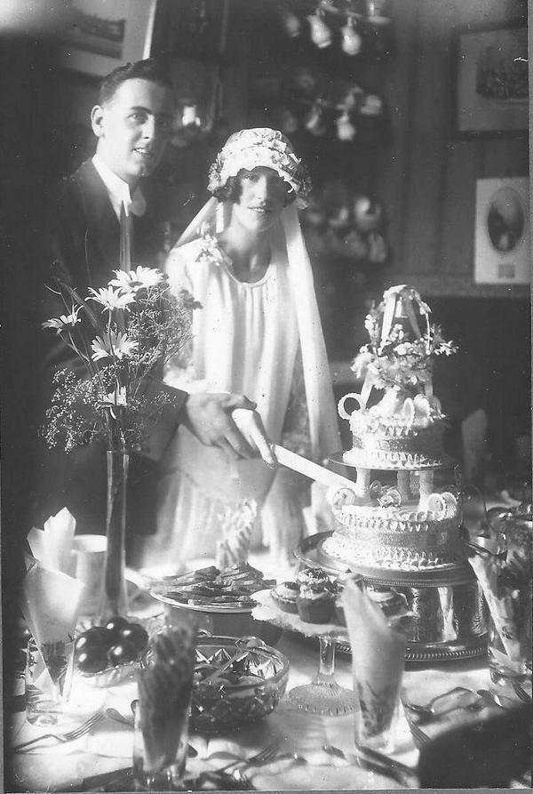 Groom and Bride cutting their cake in the 1920's.