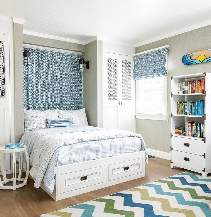 White Lattice Wardrobe Cabinet Doors Flank A Blue Tapestry Headboard Lit By Cage Sconces Mounted In White Sofa Living Room White Wainscoting Boy Bedroom Design