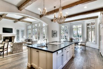 Open concept floor plan for Kitchen, Breakfast, and Living Room areas. Large windows and French doors allow lots of natural light to pour in. Warm neutral color scheme, custom reclaimed oak wood flooring, rough-sawn wood ceiling beams, soapstone slab countertop on kitchen island with built-in paper towel holder, undermount bar sink, and inset cabinet doors. (image by Parker House Inc., via Houzz)