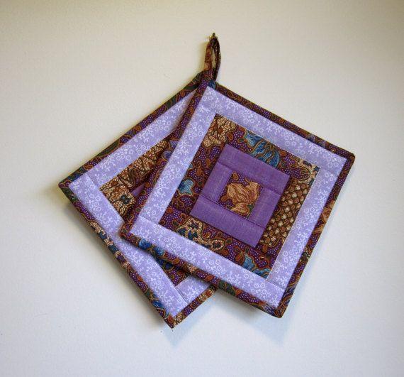 Dieser Satz von 2 gesteppte Topflappen besteht aus Webkanten von 3 verschiedenen Stoffen: eine lila Fantasie floralen Design, einem kleinen Blumenprint in Lavendel und ein mittleres lila Stoff in ein kreisförmiges Design angeordnet. Der zentrale Platz ist ein gelb getönten Blüte aus der lila Stoff, den ich auch für den Rücken und die Bindung verwendet. Andere Farben sind ein mittelbraun und Hauch von blau und dunkelblau mittelgrün. Es gibt zwei Schichten von Wimper (hitzebeständig…