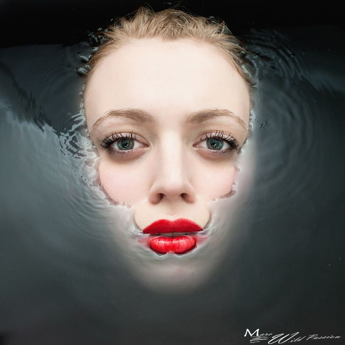 A extremely striking portrait of a women's face partially submerged in water- I love the contrast of the eyes, her red lipstick and the water. Image by Marc Lamey.