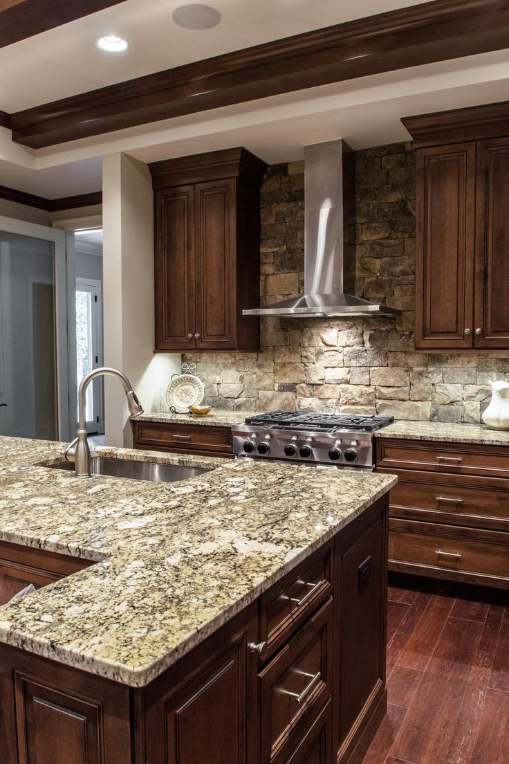 Custom wood cabinets and gray, stone countertops are top-of-the-line finishes featured in this elegant yet rustic kitchen. A stacked stone backsplash creates a cozy, rustic style feel.