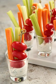 Homemade dill dip served in a shot glass with carrots, celery and speared baby plum tomatoes.