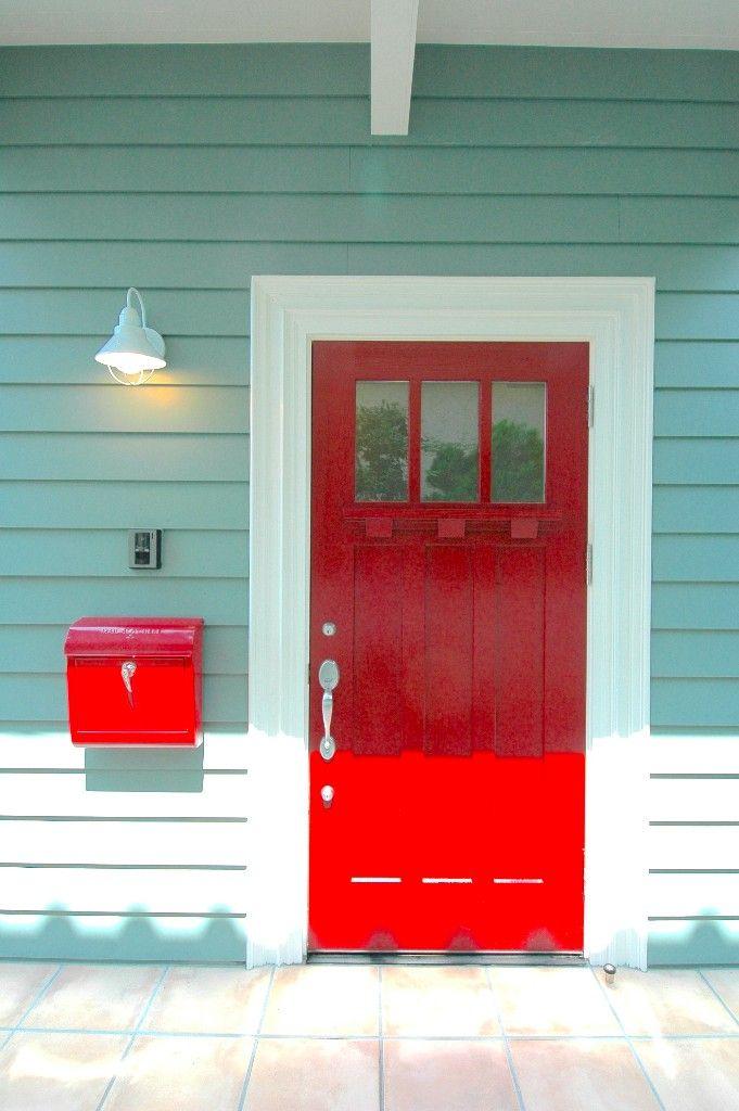 ミントグリーンの外壁にビビットな赤いドアが映えるカラフルな玄関