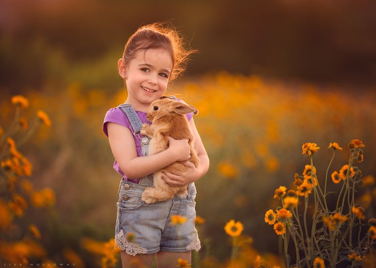 A cute little girl holds a pet bunny in a field of yellow wildflowers outdoors for a portrait ljholloway photography is a las vegas child photographer