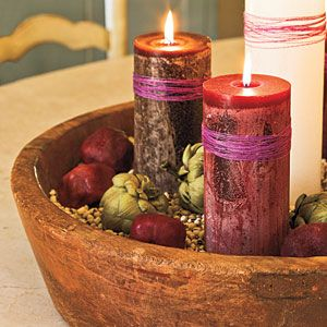 Pull together a quick and easy advent wreath by grouping pillar candles wrapped with strands of thread and arranging them in a large wooden bowl filled with dried black-eyed peas, pomegranates, and artichokes.