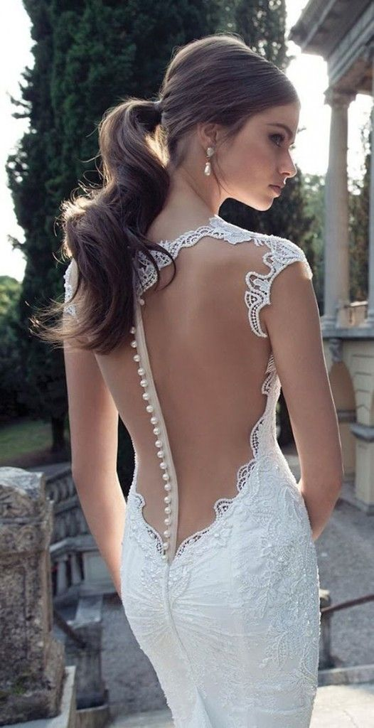 A low ponytail with a backless wedding dress with pearls for a modern bride.