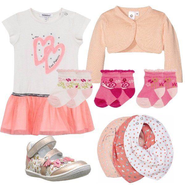 Per una passeggiata con la nostra piccolina, scegliamo un look dai colori tenui, con vestito rose, cardigan color pesca, scarpe di pelle con chiusura a strappo multicolor, calze sui toni del rosa e bavaglini abbinati al look.