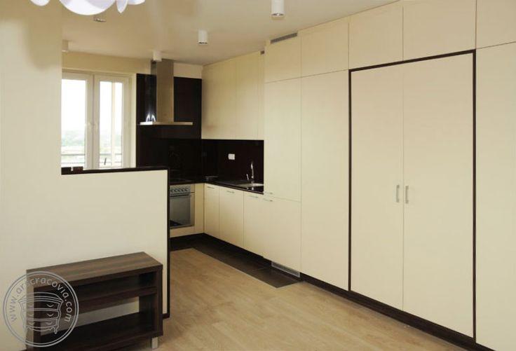 Kuchnia w małym mieszkaniu, połączona z wysoką zabudową szaf, całość w jasnym pastelowym kolorze, który nie zmniejsza optycznie przestrzeni mieszkania.