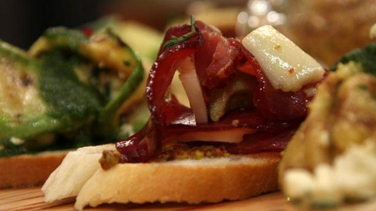 Etli Ekmek Üstü Malzemeler: 100 gr. kuru et( isli çerkez eti) 10-15 adet Antakya kırık zeytin 3-4 adet yağda kuru domates 1 tutam taze kekik yaprağı 2 yemek kaşığı zeytinyağı 1 diş sarımsak 100 gr dil peyniri 8-10 dilim baget ekmek 2 tatlı kaşığı taneli hardal