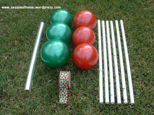 "Outdoor Holiday Lolipops Rubber play balls in red and green, wired ribbon, clear cellophane (the kind you wrap ""gift baskets"" with or use pre-formed ""gift basket"" plastic bags (Dollar Tree), PVC pipe (cut in equal lengths; I chose 3 ft. for my garden) to be used as the lollipop stands, large suction cups, strong adhesive, wired holiday ribbon, thin wire or pipe cleaners."