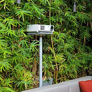 Ten took his setup very seriously, connecting an LCD projector to his indoor entertainment center via underground cables. Outdoor speakers are mounted to a fence behind the bamboo. The movie screen hangs on the garage wall 15 feet away and rolls up into a sheet-metal cover under the eaves when not in use.