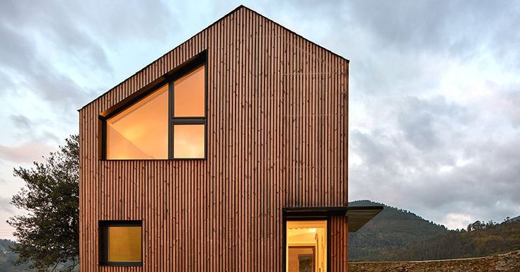 The modern home features a facade of wood slats, recessed windows, and a floating staircase.