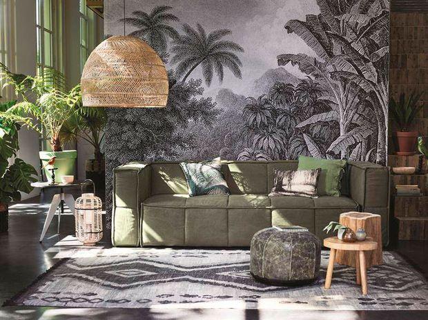 Salón decorado con plantas y sofá verde de HKLiving