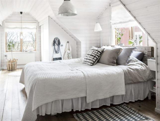 <span>Rogivande sovrum. Egensnickrad sänggavel av gamla plankor. Gaveln ger en skön känsla i rummet. Under snedtaket finns praktiska platsbyggda garderober.</span>