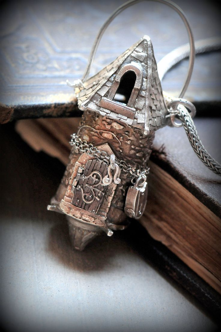 Rapunzel's tower by Christi Anderson. As a part of the Fairy Tale series, the Rapunzel's Tower Locket is the crowning glory. It is Solid Sterling with an opening door and removable top. The lock chained around the tower is handmade from fine silver. From the tip of the tower to the bottom it measures just about 3 inches. The width is a little over an inch. It comes on a heavy sterling silver 32 inch chain.