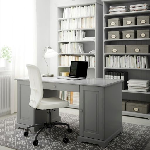 A home office with a grey desk, bookcases and a swivel chair with white cotton cover