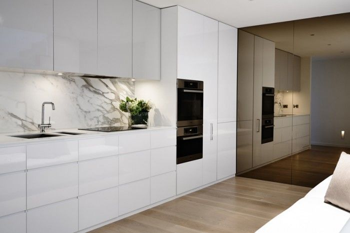 Smoked bronze mirror wall contrasting crisp white cabinetry and marble backsplash
