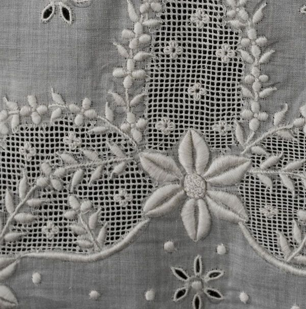 Hand-embroidered blouse panel, c.1900 -  The lady who made her own clothes or had a dressmaker to make them in the early 20th century could purchase panels of cloth that were hand embroidered with neckline and sleeve decorations. The panels, sold in dry goods stores, were coordinated with matching plain cloth. This one features exquisite three-dimensional hand embroidery with a variety of textured stitches. - Vintage Textile