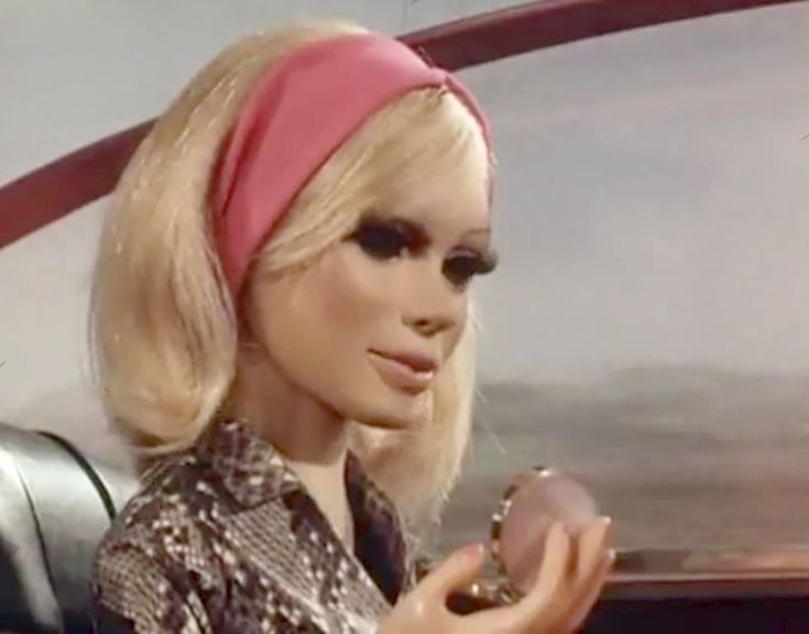 Lady Penelope with her powder compact and wearing a very 1960s headband...notice tha naugahide upholstry?!