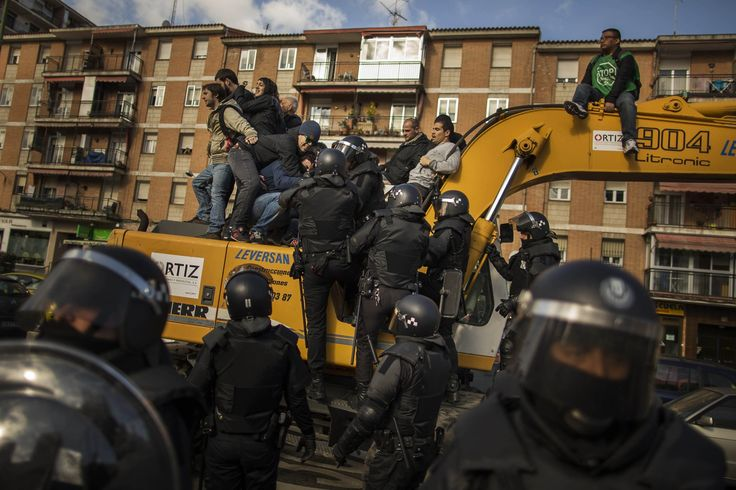 In Madrid, riot police remove housing rights activists from a bulldozer as they attempt to stop Luisa Gracia Gonzalez and her family's eviction and the demolition of their house. Evictions in Spain have soared since the country's economic crisis began in 2008, as increasing numbers of people have become unable to meet mortgage payments.