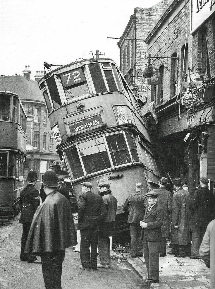 """The aftermath of a Tram accident in April 1946. An early morning """"Workman's"""" Tram gathered speed down Grand Depot Road and derailed at a crossover and plunged into the Co-op in Woolwich New Road. Four people received minor injuries. The local police seem to have it well in hand. The Workman's Tram was introduced by the London County Council when that body ran the most of London's Trams. They were early morning Trams which catered for factory workers at cheaper fare rates. It was also…"""
