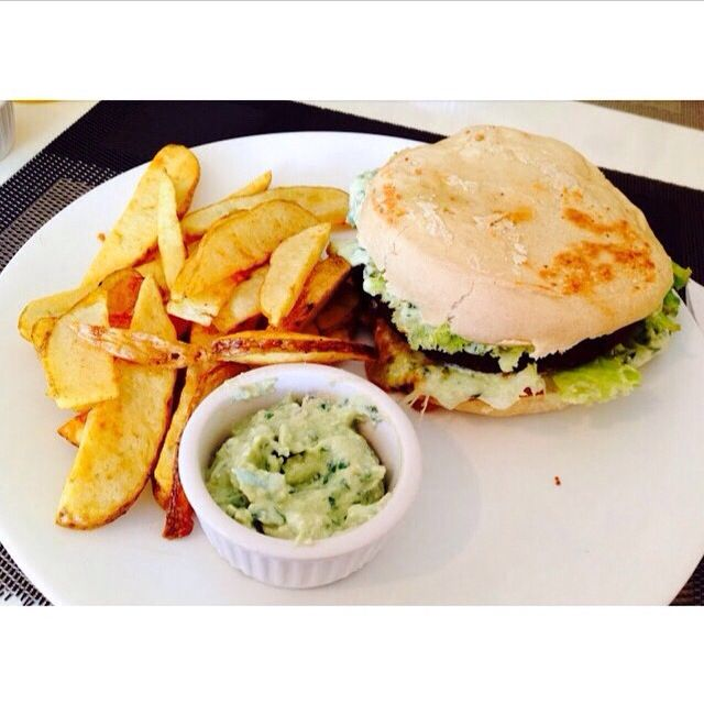 Delicious vegan burger accompanied by some potatoes and a garlic-basil dip.