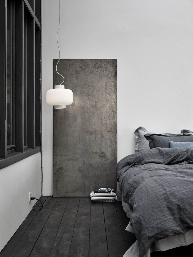 The matte black floorboards, the hues of dark and light grey stonewashed linen on the bed, the sheet of metal against the wall that becomes art