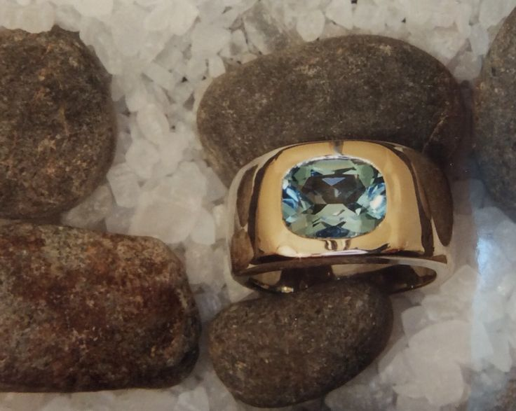 wide dome ring featuring flush set antique shape Aquamarine in yellow gold with fine white gold accents