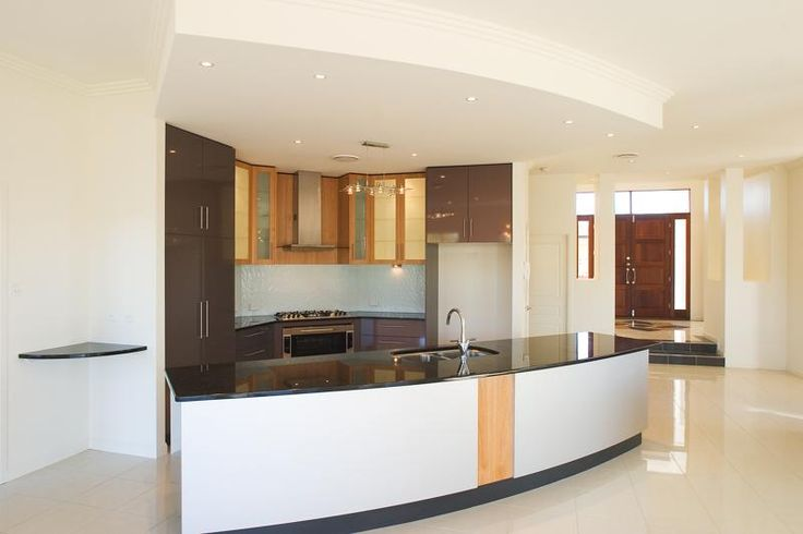 Curved island bench with interior lighting to overhead cabinetry