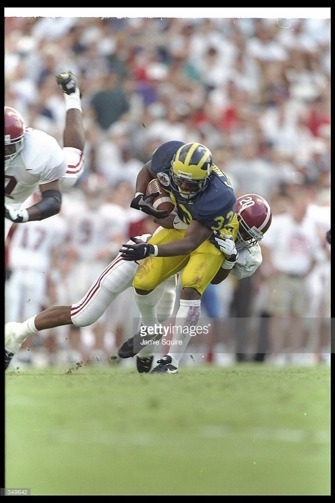 Running back Clarence Williams of the Michigan Wolverines gets tackled by Alabama Crimson Tide player Kelvin Sigler during the Outback Bowl in Tampa, Florida. Alabama won the game, 17-14.