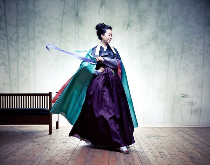 HANBOK BY LYNN: Various shades of purple, giving off feminine elegance, fanciness, and grace, have been used as the color of royal family from long ago. The purple chima, and jeogori (skirt and jacket) along with the contrasting emerald durumagi (traditional Korean overcoat) add to the mystique of this look. Designed by Min-Jeong Kim.