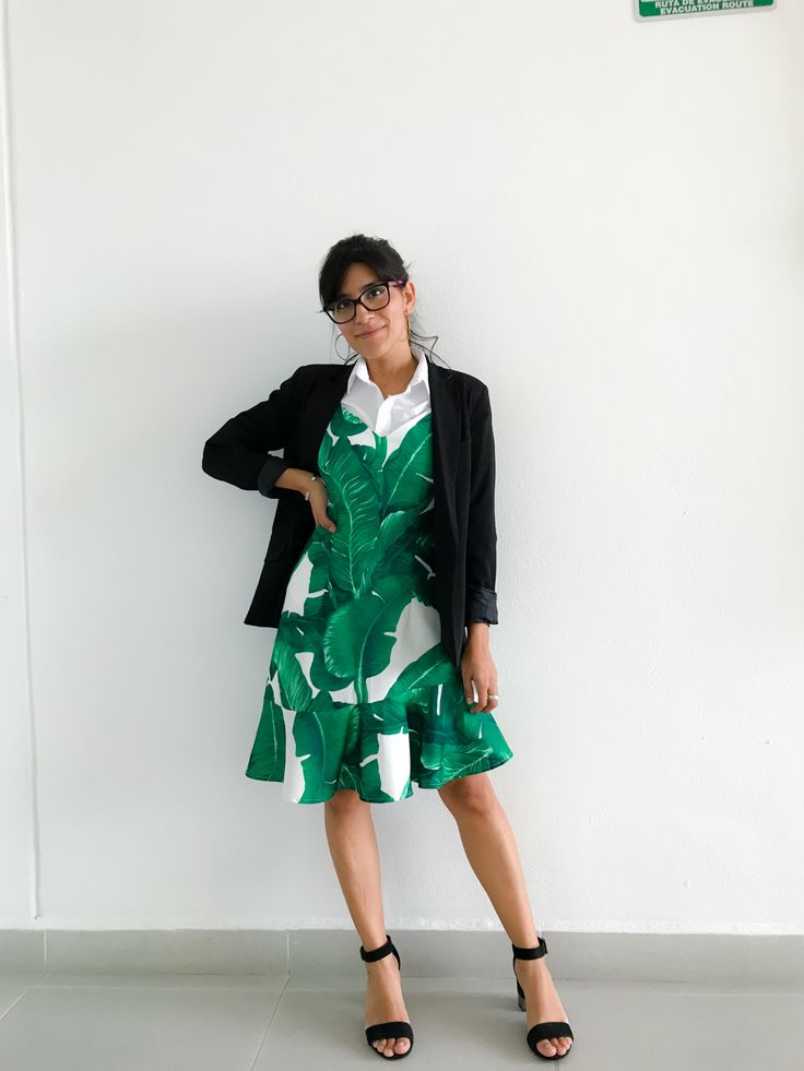 Outfit Godinez: Vestido con estampado de palmeras, combinado con una camisa formal blanca. tacones negros y blazer negro.