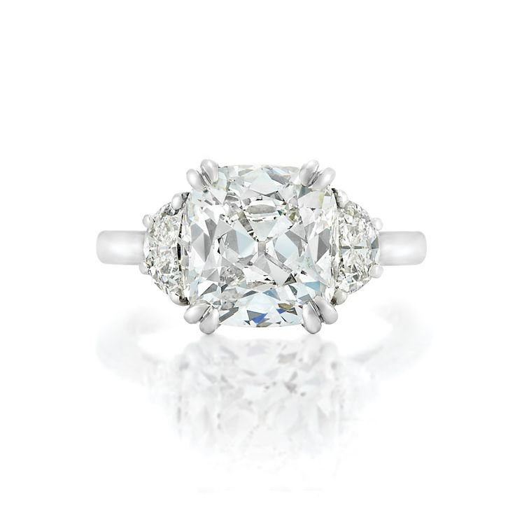 Platinum and Diamond Ring  Centering one cushion-shaped brilliant-cut diamond approximately 5.05 cts., flanked by 2 half moon-shaped diamonds.