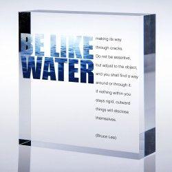 """Cubetto plexi con la frase di Bruce Lee """"Be like water making its way through cracks"""", un invito alla flessibilità mentale."""