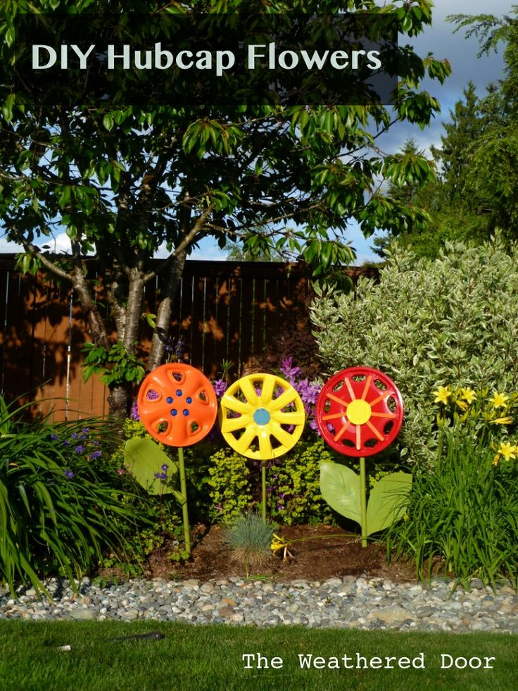 """The Weathered Door: Hub caps as flower yard art! I am so in love with these! what a fabulous way to """"recycle!""""  @Katie Helton- thought you might like these too!"""