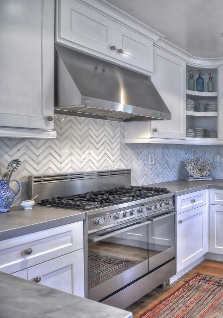 Modern marble backsplash in a white kitchen.