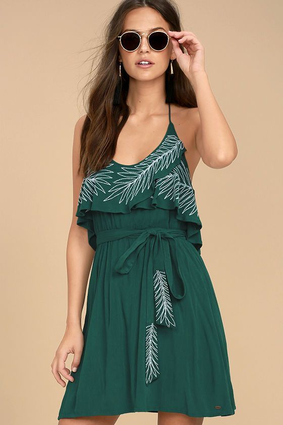 Give your look a little island flavor with the O'Neill X Natalie Off Duty Valerie Teal Green Embroidered Dress! Gauzy woven fabric falls from a tying halter neckline into a flounce bodice with white leaf embroidery. Elasticized waist with tying sash tops a full skirt. Metal logo tag at side.